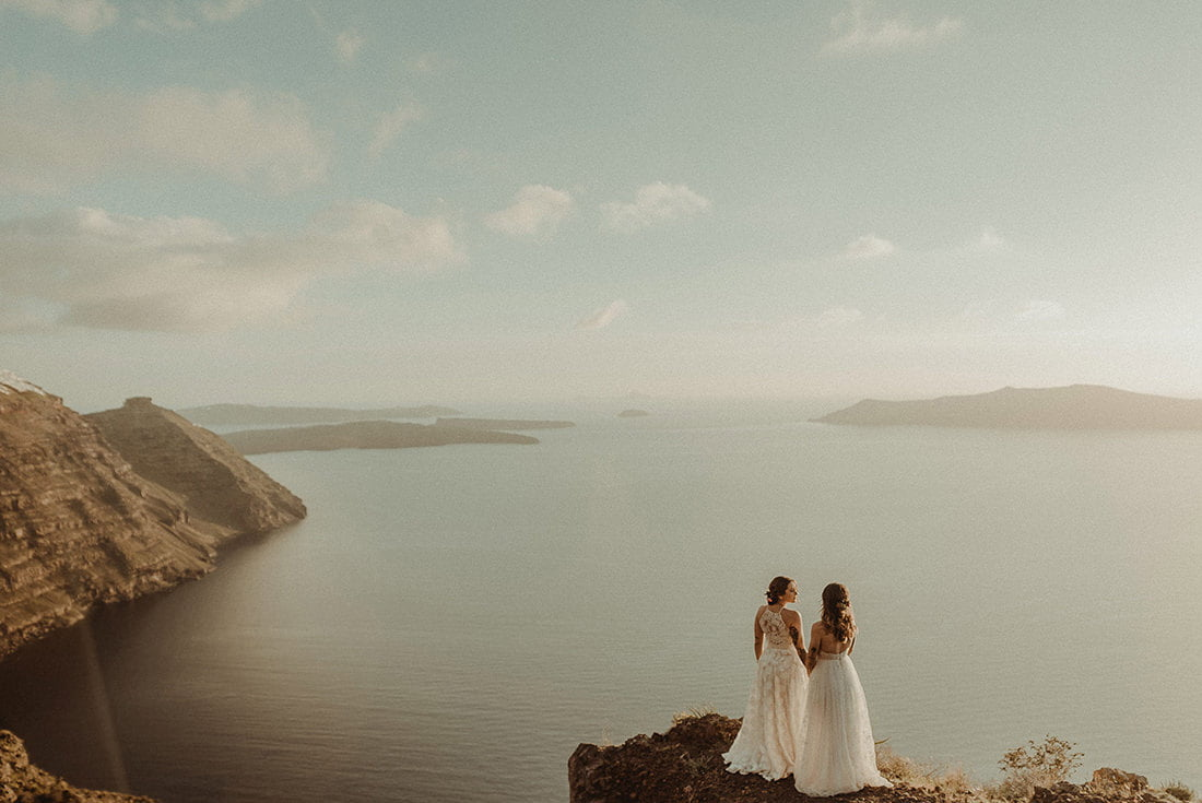 Stunning couple of two brides in Imerovigli illustrating the guide of best places to get married in Santorini