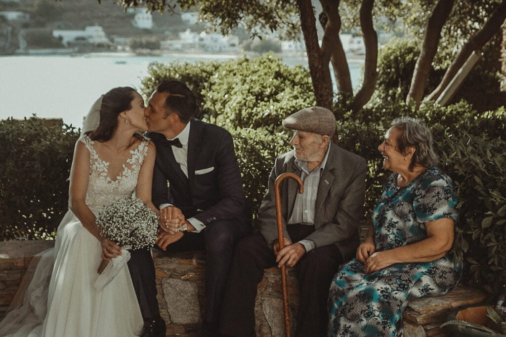 Kythnos wedding couple kissing while an elder couple looking