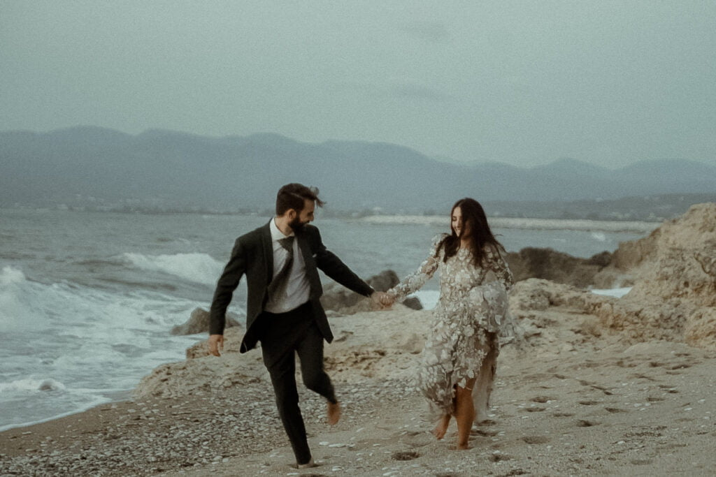Artistic couple running on the beach filmed by an alternative wedding videographer for a visual poetry wedding film