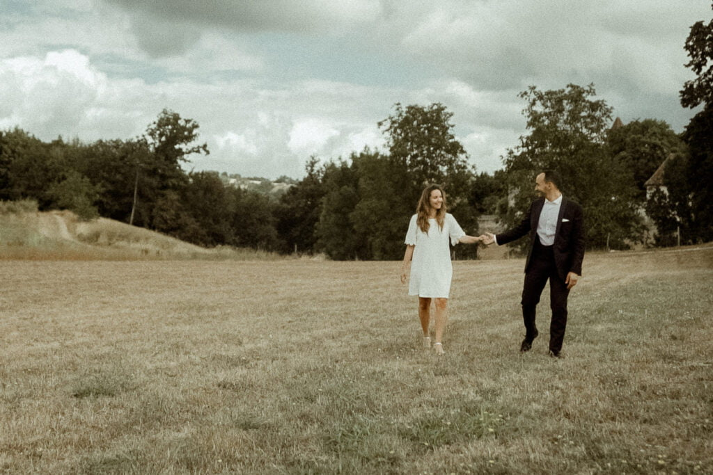 Wedding couple walking in the french countryside in front of the Chateau Chapeau Cornu for their wedding video