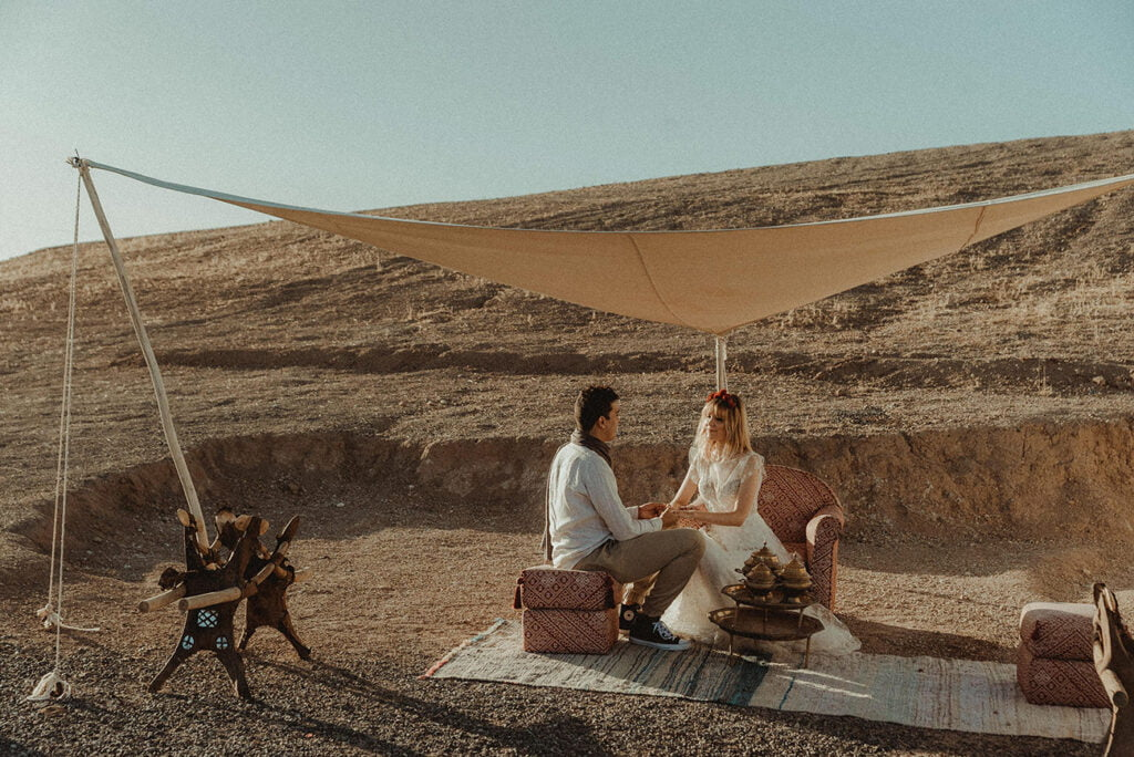 Destination Wedding couple enjoying tea in the desert of Morocco
