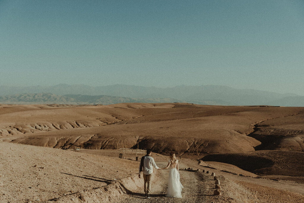 Couple walking in the Moroccan Desert for their destination Wedding Ceremony