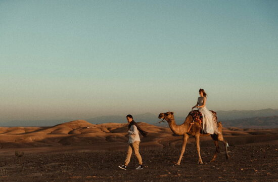 Morocco Elopement Wedding Couple walking in the Moroccan Desert with a dromedary